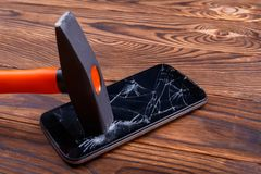 Hammer hits the smartphone on the broken screen. On a wooden background. Close-up. A heavy construction hammer with an orange padded hilt hits the modern black stock photo