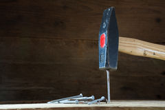 Hammer hitting a nail, dark wooden background with copyspace Royalty Free Stock Photography