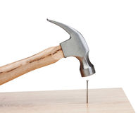Hammer hitting a nail into a wood. Isolated on white background Stock Photos