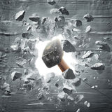 Hammer hitting the wall. Causing hole and debris Stock Photography