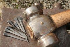 Hammer and horseshoe nails. Strong heavy hammer and eight horseshoe nails rest on the anvil Royalty Free Stock Photo