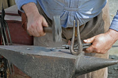 Hammer on Iron -Schmied Stock Photo