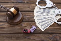 Hammer of the judge, dollars, handcuffs. two collided cars. On a wooden background. auto insurance. damage to property Royalty Free Stock Photos