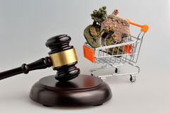 Hammer of judge with model of house in trolley on gray Stock Image