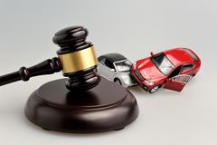 Hammer of judge with models of car accident on gray. Background stock image