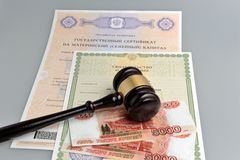 Hammer of judge with money, maternal and birth certificates on g Stock Photo