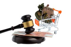 Hammer of judge with money and model of house in trolley isolate Royalty Free Stock Photos