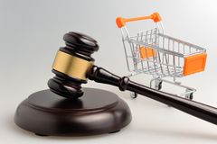 Hammer of judge and pushcart on gray Stock Photography