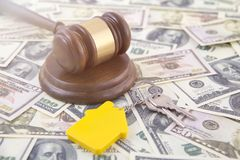 Hammer judges, keys with a keychain in the form of a house on the background of banknotes. Breaking the law, real estate stock photo
