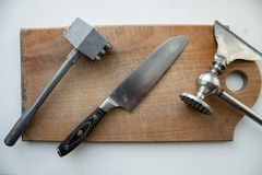 A hammer meat and knife and kitchen ax on a wooden deck stock photos