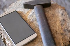 A hammer lies next to a mobile phone stock images