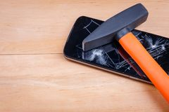 A hammer is located on smartphone with a broken screen. Close-up. The concept of electronics repair. A construction hammer with an orange padded arrow is royalty free stock photo