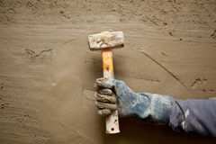 Hammer man with gloves in grunge cement background Royalty Free Stock Images