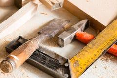 Hammer, Meißel und Winkeltischler liegen auf einem Werktisch Stockfotografie