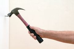 Hammer and nail. View of a hand holding a hammer striking a nail Royalty Free Stock Images