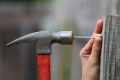 Hammer and Nail. Close up view of a black and red hammer being used to hammer a nail into a fence post Stock Photo