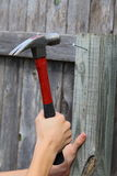 Hammer and Nail. Close up view of a black and red hammer being used to hammer a nail into a fence post Stock Photos