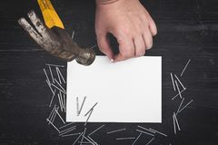 Top view on the hand holding hammer, scattered nails, blank sheet of paper on black wooden table. Royalty Free Stock Images