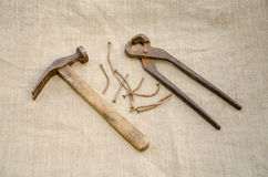 Hammer with nail and pliers lying on linen texture Royalty Free Stock Photo