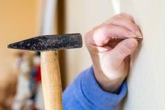 Hammer a nail into a wall close up Stock Photos