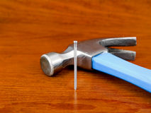 Hammer and nail on wooden background Stock Photos