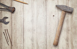 Hammer and nail on a wooden surface with space for text. Pliers, pen, wrench and nails beside Royalty Free Stock Photography