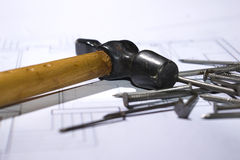 Hammer and nails. Photo of the hammer and nails on the house plan Royalty Free Stock Photo