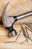 Hammer and nails. Closeup of a hammer and nails laying on lumber Royalty Free Stock Photography