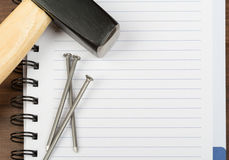 Hammer with nails on blank note pad Stock Image