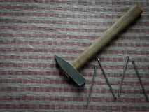 Hammer with nails on brown wood table stock photos