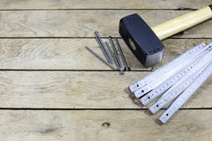 Hammer, Nails And Folding Ruler On Wooden Plank Royalty Free Stock Images