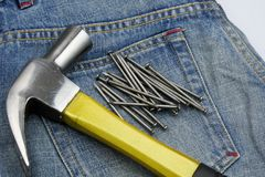 Hammer and nails on jeans Royalty Free Stock Photo