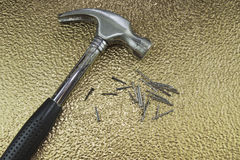 Hammer and nails. Metal hammer with nails on gold textured sheet Stock Image