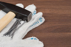 Hammer and nails on protective gloves Royalty Free Stock Photos