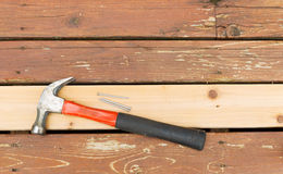 Hammer and nails on top of new cedar wooden board Royalty Free Stock Photo