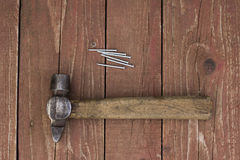 A hammer and nails. Vintage hammer and nails on a wooden surface Stock Images