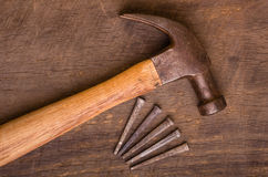 Hammer and nails on a wood board Stock Image