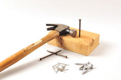 Hammer, nails and woodblock. Hammer resting on woodblock with different nails on the ground stock images