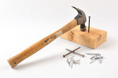 Hammer, nails and woodblock. Hammer resting on woodblock with different nails on the ground stock photo