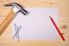 Hammer and nails on wooden background with sheet of paper Stock Photos