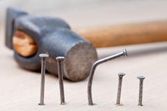 Hammer nails into wooden board Stock Images