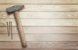 Hammer and nails on a wooden surface with space for text Stock Photography