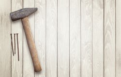 Hammer and nails on a wooden surface with space for text Royalty Free Stock Images