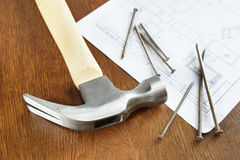 Hammer with nails on the wooden table Royalty Free Stock Photo