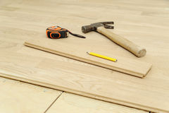 Hammer, pencil, measuring tape or flooring. Royalty Free Stock Photography