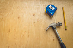 The hammer, pencil, roulette lies on a wooden surface. Hammer, pencil, tape measure and saw on wood Royalty Free Stock Images