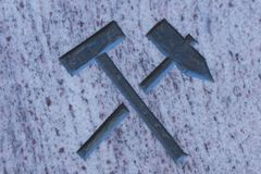 Hammer and pick on stone surface. Symbolizing the alliance of workers and peasants.  Symbol of mining Royalty Free Stock Photography