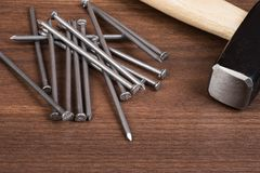 Hammer with pile of nails on table. Hammer with pile of nails on brown wood table Royalty Free Stock Photography