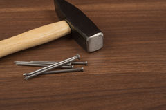 Hammer with pile of nails on table. Hammer with pile of nails on brown wood table, front view Royalty Free Stock Photos