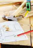 Hammer and a plan with pencil lie on the workbench Royalty Free Stock Photos